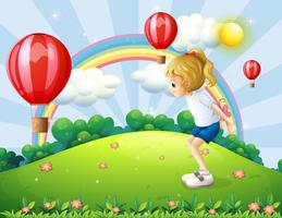 A girl playing in the hill with floating balloons