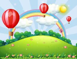 Palloncini galleggianti in cima alla collina con un arcobaleno