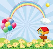 A garden near the hills with balloons, a rainbow and a pet house