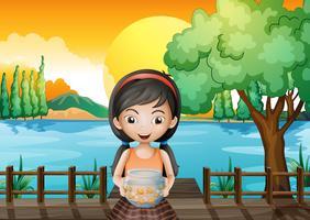 Una niña en el puente con un acuario.