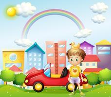 Een jonge jongen met een rubberen eend en zijn auto voor de hoge gebouwen