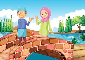 A Muslim couple waving at the bridge