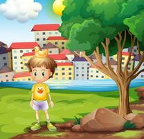 A boy with a rubber duck above his head standing near the tree