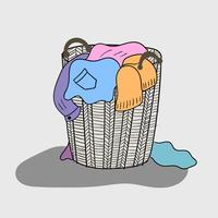 A variety of colored clothes are mixed in a wooden basket that looks dirty