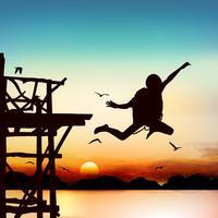 Silueta y niño saltando en el crepúsculo con cielo azul.