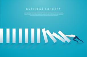 Hombre de negocios que detiene el efecto dominó. concepto de negocio