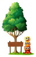 Tres monstruos jugando cerca del letrero de madera debajo del árbol.