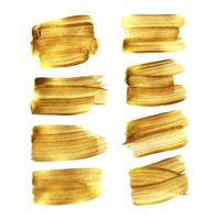 Insieme dello striscio del colpo del pennello dell'oro isolato su fondo bianco