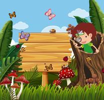 Holzschild und Junge, die Wanzen im Garten betrachten