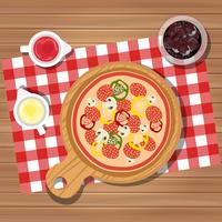 Pizza on table with bottles of ketchup and mayonnaise served with glass of juice with ice. Served dinner on table, top view