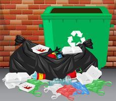 Cestino e mucchio di rifiuti sporchi sul pavimento