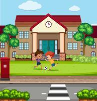 Pojkar spelar fooyball framför skolan