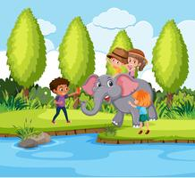 Kids riding elephant in nature
