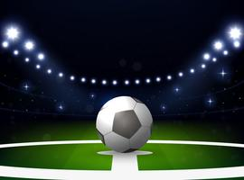 Estádio de futebol com bola e holofotes à noite
