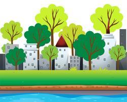Stadsbyggnader och träd längs floden