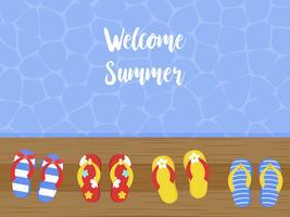 Bienvenido verano, chanclas en terraza de madera junto al mar.