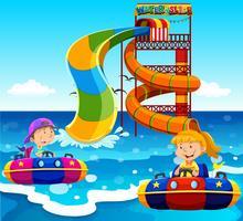 Jongen en meisje rijden op water glijbaan in de oceaan