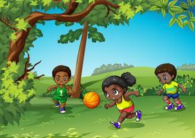 Trois enfants jouant à la balle dans le parc