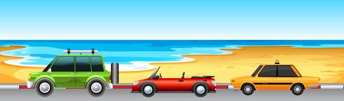 Tre bilar parkerar vid stranden