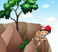 Pojke som klättrar upp klippan