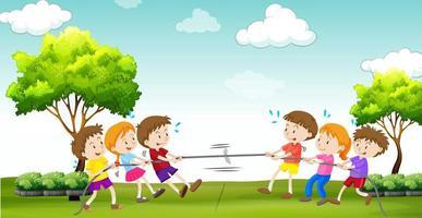 As crianças brincam cabo de guerra no parque