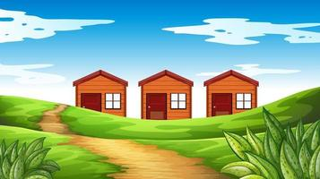 Three wood houses on the field