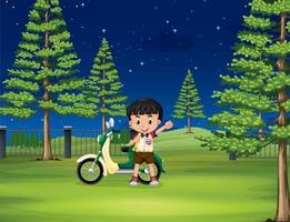 Boy and motorcycle in the park at night