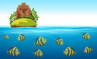 Escena con peces nadando bajo el mar con isla arriba