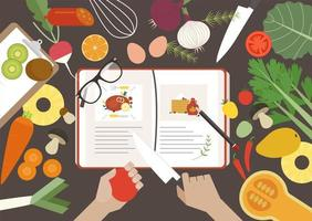 Vista superior del libro de recetas y verduras en la mesa