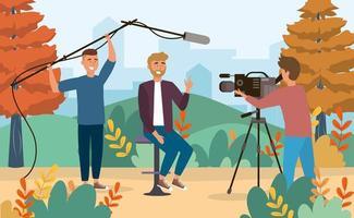 Repórter masculino e cinegrafistas no parque