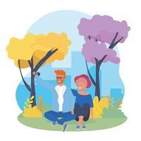 Junge Paare, die selfie im städtischen Park nehmend sitzen