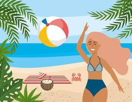 Woman playing with beach ball on beach