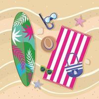 Vista aerea della tavola da surf sulla spiaggia con boccaglio, cappello, asciugamano e borsa