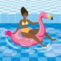 Joven mujer afroamericana en traje de baño en flotador flamenco