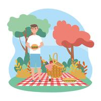 Man holding sandwich on picnic blanket