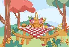 Picknickkorg med bordduk och mat på bordet parkerar in