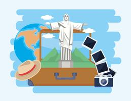 Christ the redeemer statue in suitcase with camera and hat