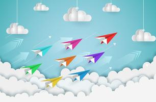 Colorful paper planes flying above clouds
