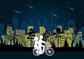 Homens e mulheres pedalam na estrada à noite
