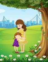 En mamma och hennes dotter under trädet