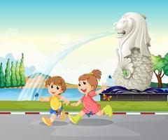 Två barn som leker nära statyn av Merlion