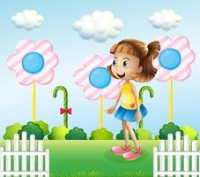 A little girl near the wooden fence with giant candies