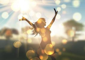silhueta da mulher contra a paisagem desfocada iluminada pelo sol