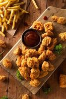 Crispy popcorn chicken and fries on a wood board