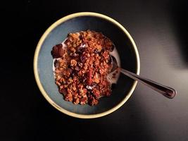Homemade pumpkin granola with milk and spoon on dark background