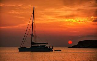 Silhouette of a sailing boat at sunset, in Syros Greece