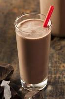 Glass of chocolate milk with red straw on a wooden table