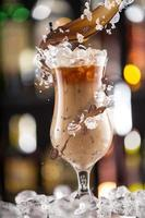 Cold coffee drink with ice, beans and splash photo