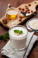 Milkshake or banana smoothie with almonds, oat, honey and mint photo