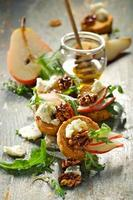 Canapes with blue cheese, fresh pear, caramelized walnuts and arugula